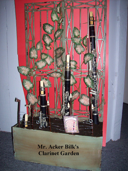 "In 1962 when clarinetist, Acker Bilk released ""Stranger on the Shore"" the lingering melody stayed with the then 9 year-old ukulele playing Rebecca. She has used that tune for testing the playability of every clarinet she learned to repair. This piece is a miniature version of the 15 foot ""Musical Garden"" that lines the walkway of her repair shop featuring clarinets, flutes, trumpets, trombones, saxophones and a 150 year-old harp. When the children ask her ""Where do you get all these instruments?"" she explains, ""I plant their mouthpieces in the spring and by fall they grow into instruments."" The piece depicts the growth of a clarinet as it grows into full maturity surrounded by its violin bow picket fence. Be sure to keep this piece watered Dimensions: 36""x 19"" x 9.5"" Price: CALL (949) 768-7110 or email admusic@cox.net"