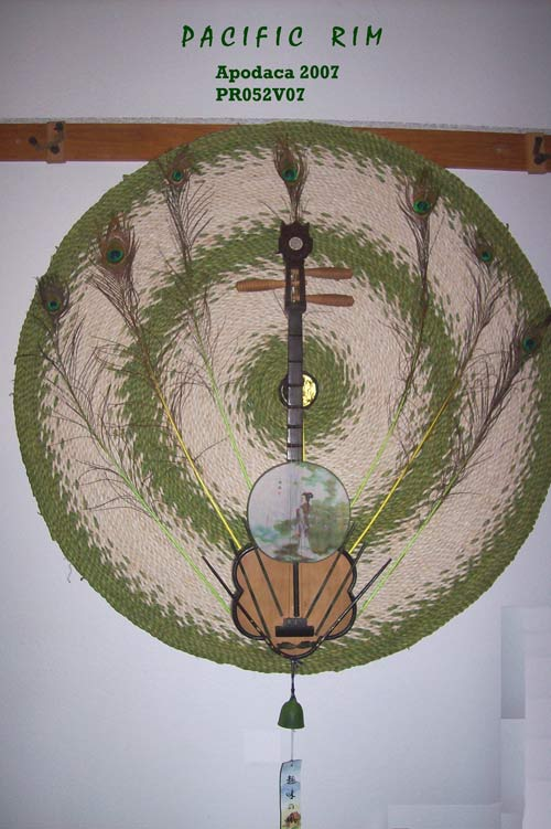 "Pacific Rim - The Asian cultures of Thailand, China and Japan are shared within this piece. A green and cream colored Chinese woven circular mat with a Ying-Yang symbol centered, works as the background. This enhances a Thai stringed instrument that is adorned with green marble chopsticks and a Japanese fan. Framing the instrument are peacock feathers. A small green soothing sounding Japanese Bell with a proverb hangs from the bottom of the piece. Rebecca's interest in the serene and minimalist arts of Asian culture has given her a respite place in her sometimes over active mind to feel calm. From the music to the art work to the manicured gardens, although she believes her Native American relatives have been here since the start of time, she knows the Bering Straight Theory could be the bases of her inner self. Dimensions: 64.5"" x 48"" x 6.5"" Price: CALL (949) 768-7110 or email admusic@cox.net"